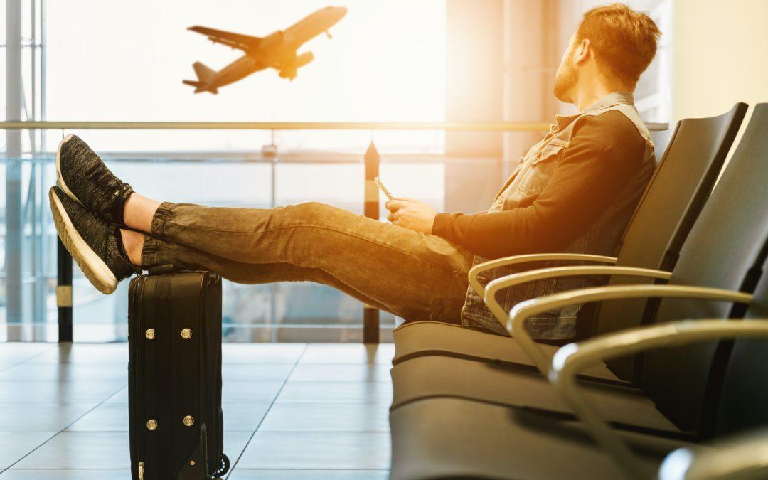 ragazzo che attende seduto in aeroporto con valigia trolley e guarda un aereo che decolla al tramonto
