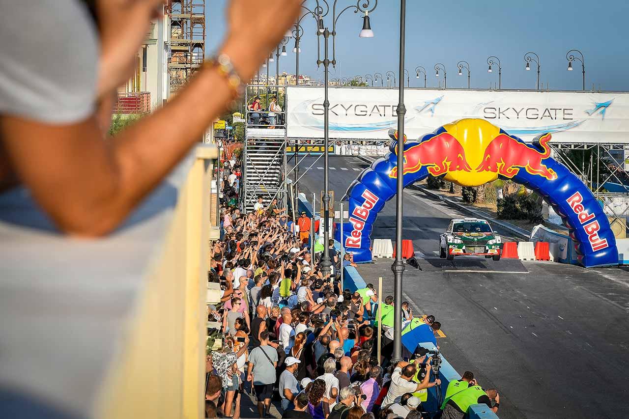 auto da rally e pubblico che assiste alla gara